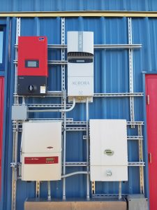 Four different inverters grouped together and mounted on blue, metal side of building, photo.