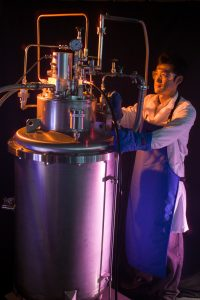 Researcher Jong Baik next to a hydrogen densification experiment in a lab, photo