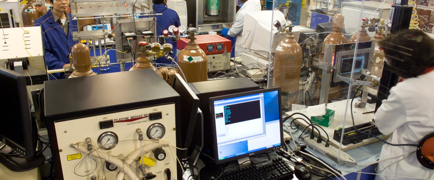 Analyzing equipment on tables within lab and three researchers in background, photo.
