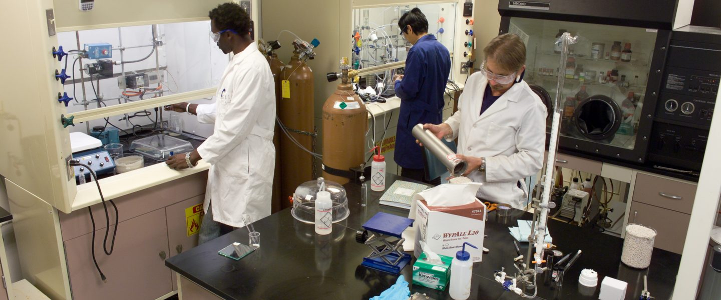 Three hydrogen researchers at different stations in hydrogen wet laboratory.