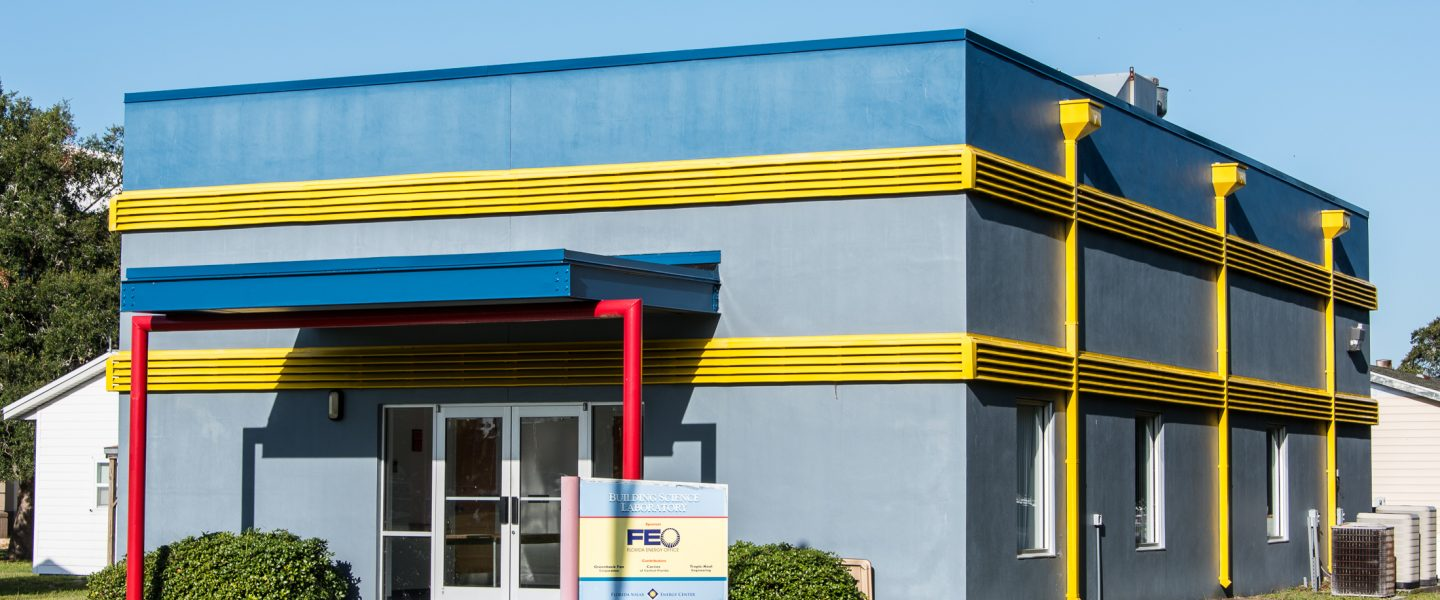 Small, one story commercial building painted in blue with yellow vents and red poles.