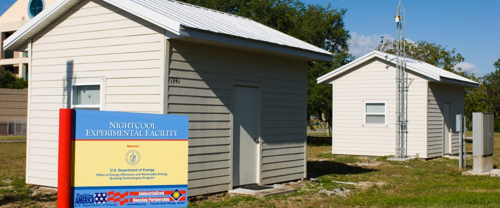 Two small buildings similar to the size of a shed, configured with different roof materials.