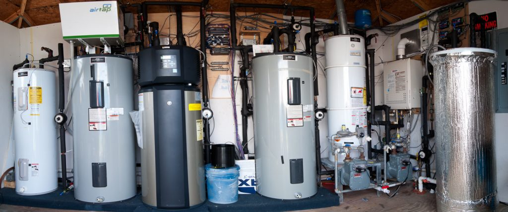 Seven water heaters arranged side by side for testing.