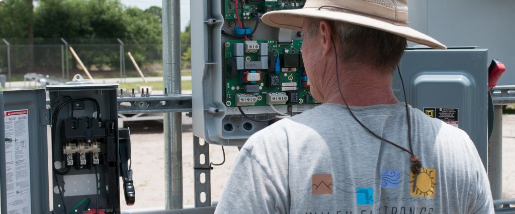 Donard Metzger inspects power connections at a test PV installation.