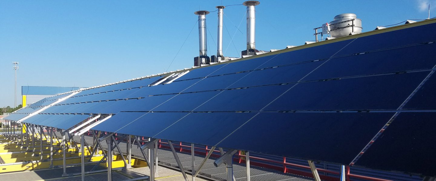Photovoltaic thin film array mounted on top oflab building with metal roof; exhaust stacks from buiding ventilation in background, photo.