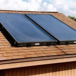 Two solar water heating panels on brown single roof.