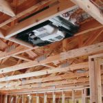 An Energy Recovery Ventilator (ERC) mounted in the wooden rafters of a new residential home under construction.