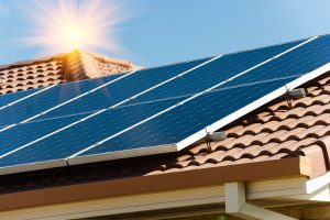 Photovoltaic panels on barrel tile roof with the sun in the background photo