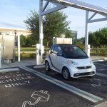 Electric vehicle charging at charging station under photovoltaic array onUCF Orlando campus
