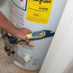 Student using a device to test for a gas leak near a gas powered water heater before a blower door test, weatherization