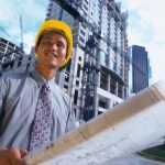 Man with yellow hardhat, holding blueprints, standing in front of tall commercial building under construction.