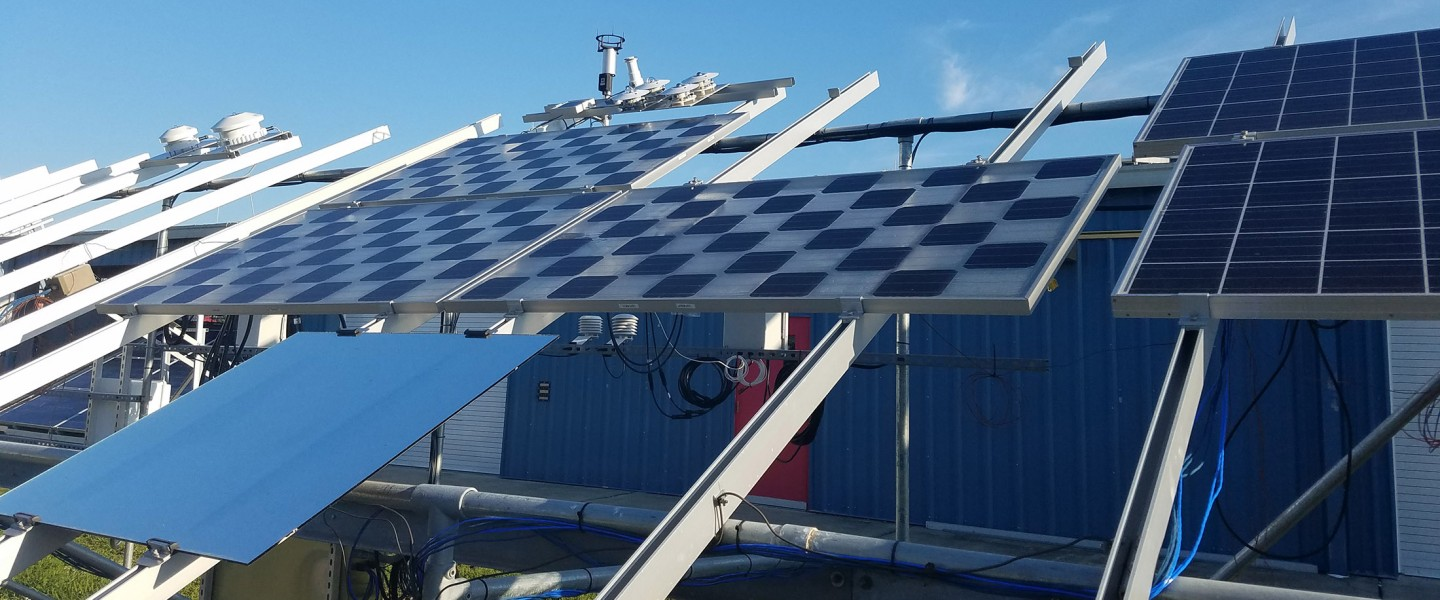 Three different types of photovoltaic modules on test rack with blue metal commercial building in background, photo.