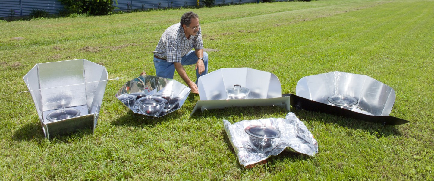 Various types of solar cookers on display with a researcher inspecting them photo