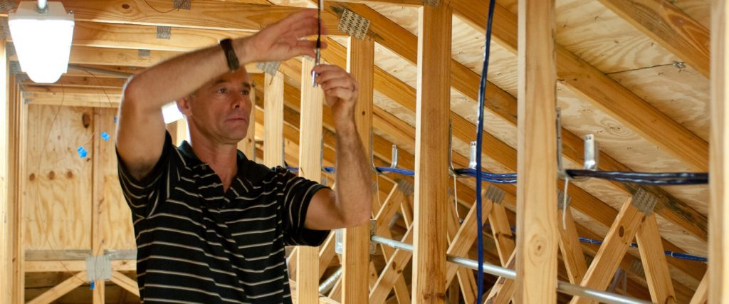UCF researcher adjusts temperature sensor in attic of Flexible Residential Test Facilty, photo.