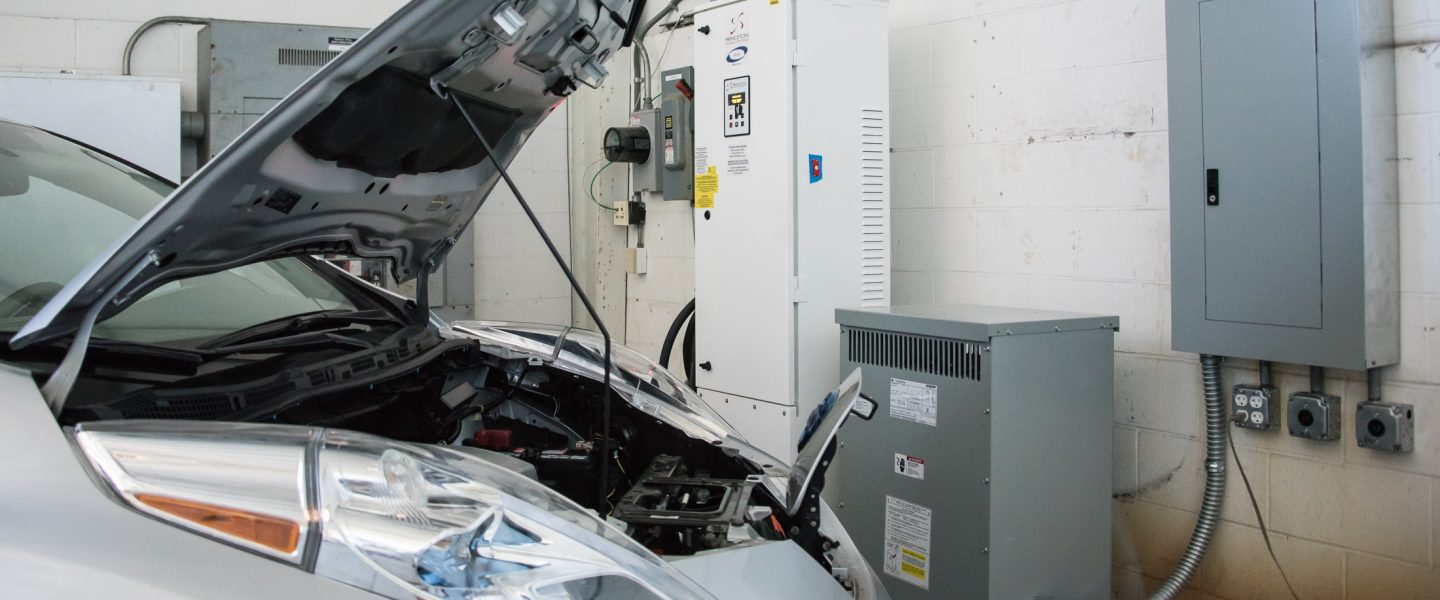 A Nissan Leaf electric vehicle has it's hood opened, charge cable plugged in, with three different charging units in the background of a laboratory, photo.