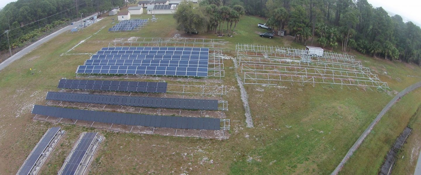 Aerial view of open grass field different types of ground-mounted photovoltaic systems, with one section with open structure to hold future PV systems; modular PV test buildings in background.
