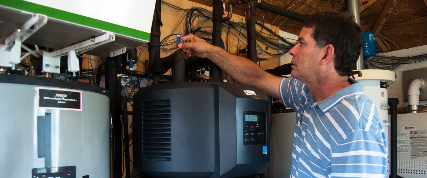 Researcher makes adjustment to the top of a data monitored water heater in side-by-side testing, photo.
