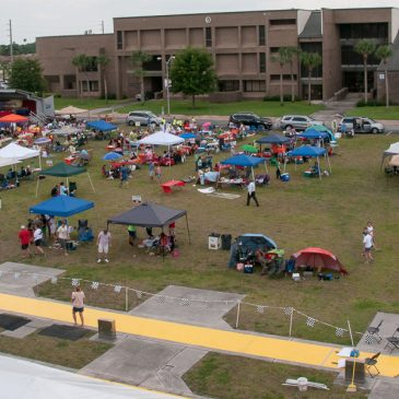 Aerial view of EnergyWhiz with yellow Junior Solar Sprint track, pop-up tents, solar cookers, and hundreds of students, photo.