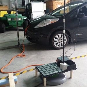 Nissan Leaf undergoing a wireless charging test in high bay workshop.
