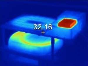 A thermal imaging camera shows the heat signature of the Plugless wireless EV charging station under test.