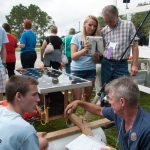 students show off their energy innovations project to judges at EnergyWhiz photo