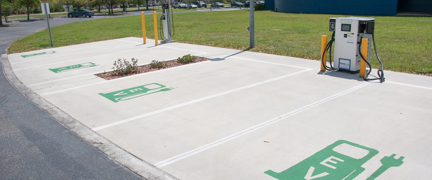 Electric vehicle public charging station–uncovered concrete pad with four parking spots–with Level 2 and Level 3 fast charger.