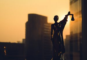 Silhouette of Themis with building background. Statuette of justice.