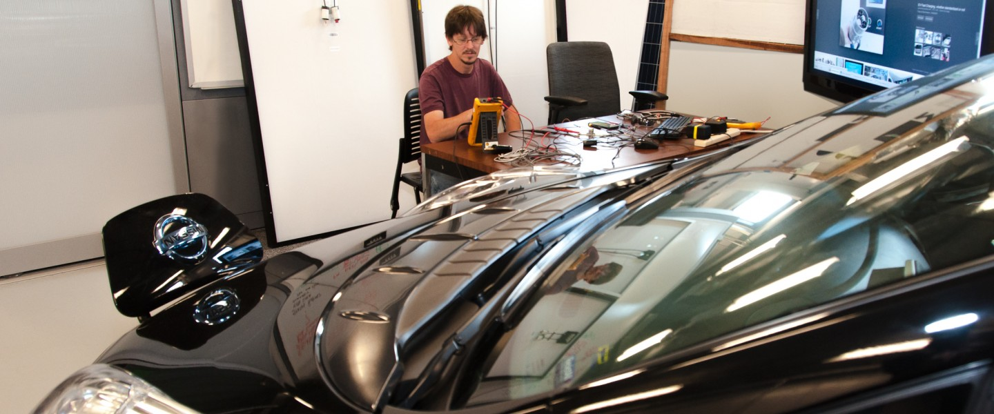 Researcher William Wilson views readouts on a Nissan Leaf EV in the lab.