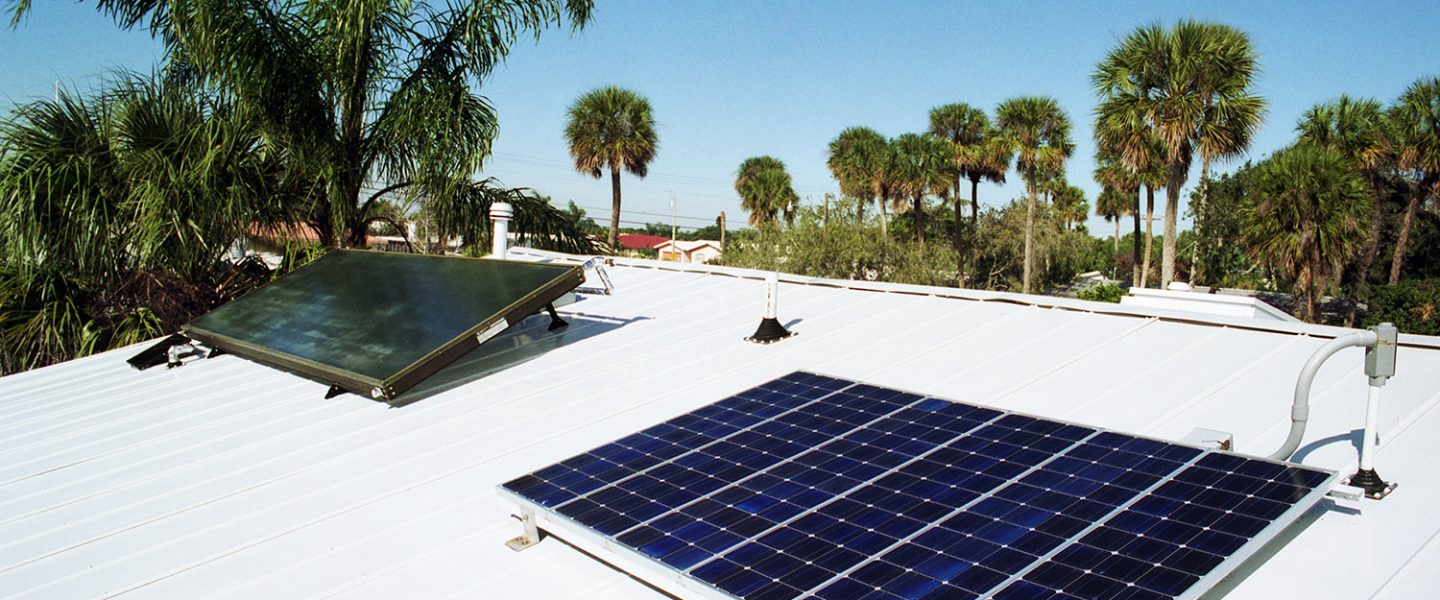 Solar water heating panel and solar electric panel on white metal roof of house with palm trees in background.