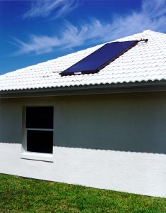 One solar water heating panel on white tile roof of house.