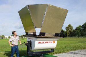 Large solar cooker oven being positioned by a researcher