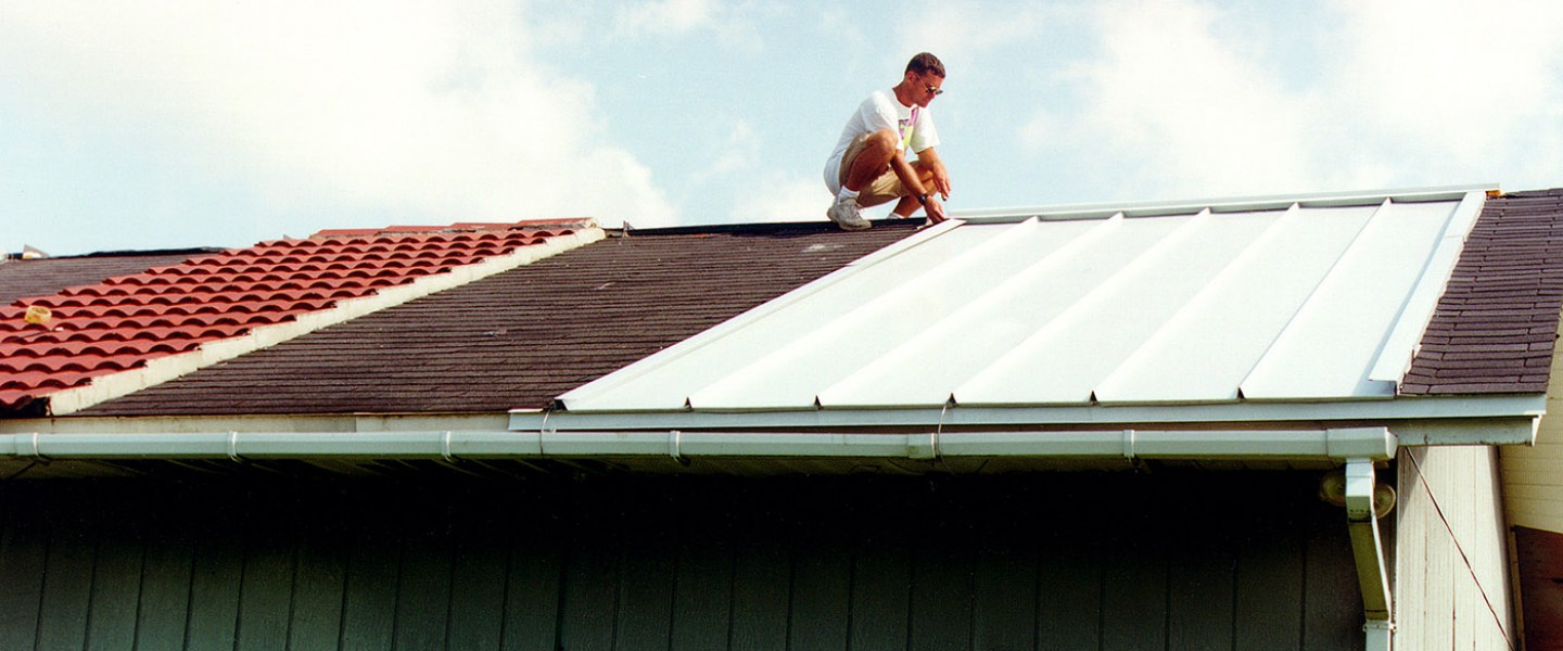A 24 ft x 48 ft frame builidng with different roofing systems; man squatted down nest to white metal roof section; photo.