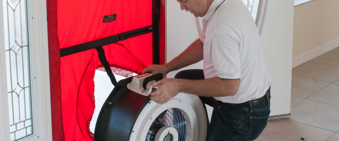 A student installing a blower door fan during an energy rater training course