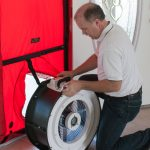 A student installing a blower door fan during an energy rater continuing education training course