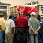 Instructor and students gathered around instructional setup using a blower door for continuing education training.