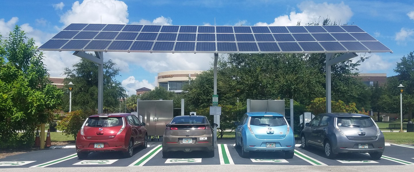 Four electric vehicles charging under photovoltaic array.