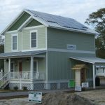 Newly-constructed factory-built modular, two-story home with covered porch and photovoltaic panels on roof.