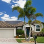 One-story, two car garage, LifeStyle Homes Net-Zero Energy Home, with palm tree in front; photo..
