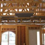 "Unfinished interior of house showing trusses and ducts constructed in a dropped or ""fur down""ceiling."