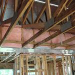 Unfinished interior of house showing trusses and ducts constructed in a raised ceiling.
