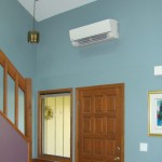 Mini split air conditioning fan above interior house door near stairway, photo.