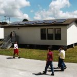 Portable classroom with solar electric panels on shingle roof with three students walking in front of while one student walks in opposite direction.
