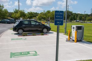 Electric Vehicle Charging Only sign next to EV charging parking spaces with chargers and black Nissan Leaf EV.