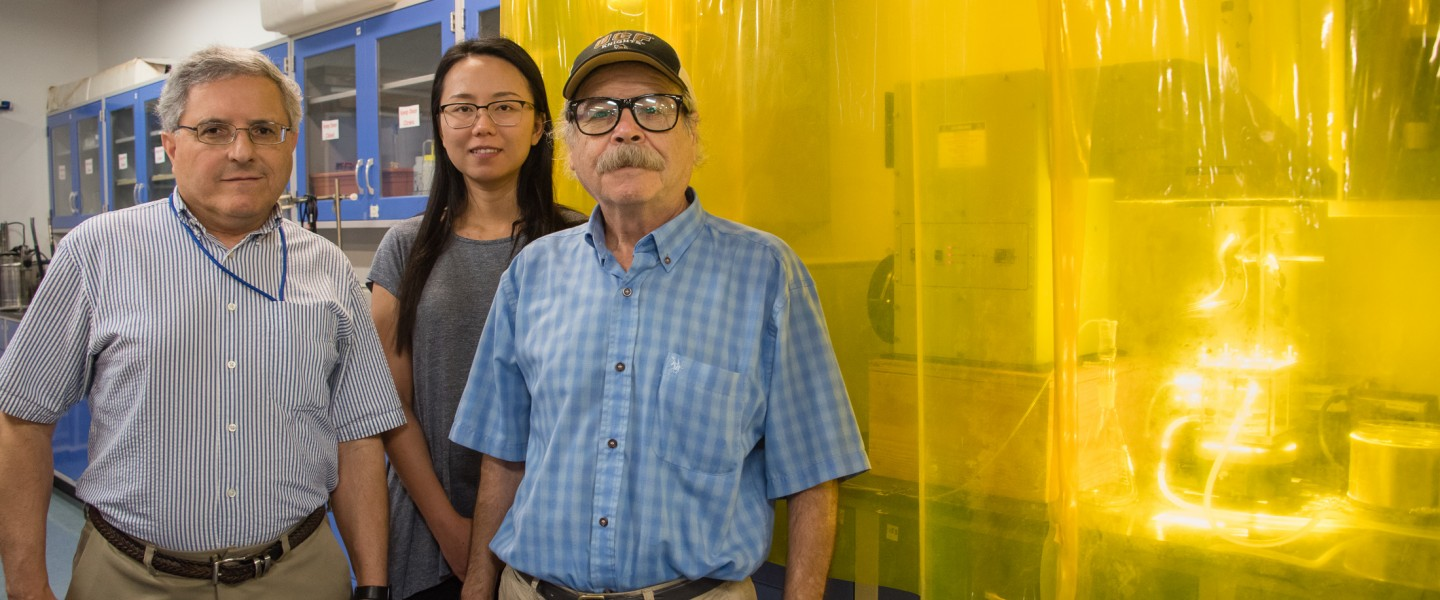 UCF researchers Ali Raissi, Nan Qin, Nazim Muradov stand alongside their solar-powered hydrogen production device, which is behind a transparent, yellow curtain in laboratory.