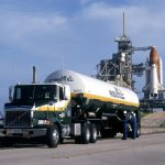 Air Products tanker of LH2 parked in front of Space Shuttle on launch pad at KSC. Two men in blue uniforms standing next to tanker.