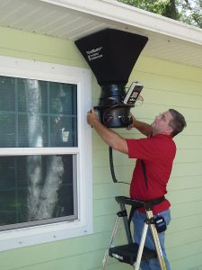 Researcher measuring outside air flow by holding Flow Blaster over outside vent in soffit overhang.