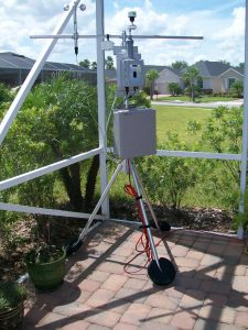 Outdoor monitoring station on ground-mounted tripod.