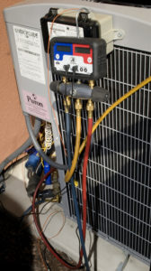 Gauges connected to outside AC unit to test refrigerant pressures